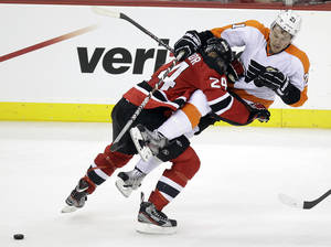 Photo -   New Jersey Devils' Bryce Salvador, left, checks Philadelphia Flyers' James van Riemsdyk during the third period of Game 3 of a second-round NHL hockey Stanley Cup playoff series, Thursday, May 3, 2012 in Newark, N.J. (AP Photo/Julio Cortez)