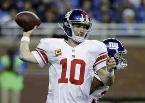 Photo - New York Giants quarterback Eli Manning (10) throws during the first quarter of an NFL football game against the Detroit Lions, Sunday, Dec. 22, 2013, in Detroit. (AP Photo/Duane Burleson)