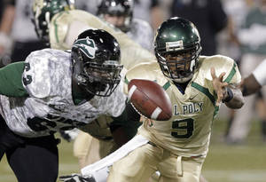 Photo - Cal Poly quarterback Chris Brown, right, flips the ball out to a running back as Portland State defender Junior Alexis moves in during the first half of an NCAA college football game in Portland, Ore., Thursday, Sept. 26, 2013. (AP Photo/Don Ryan)