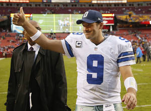 Photo - Dallas Cowboys quarterback Tony Romo flashes a thumbs-up as he walks off the field after the Cowboys defeated the Washington Redsksins 24-23 in an NFL football game in Landover, Md., Sunday, Dec. 22, 2013. (AP Photo/Evan Vucci)