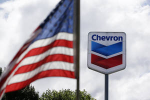 Photo - FILE - In this May 23, 2013, file photo, a United States flag flies in view of a Chevron gas station in Blaine, Wash. Chevron reports quarterly earnings on Friday,  Jan. 31, 2014. (AP Photo/Elaine Thompson, File)