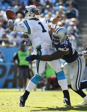 Photo -   Carolina Panthers quarterback Cam Newton (1) tries to get off a pass as Dallas Cowboys nose tackle Jay Ratliff (90) tackles him during the second half of an NFL football game, Sunday, Oct. 21, 2012, in Charlotte, N.C. (AP Photo/Bob Leverone)