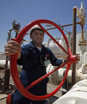 Photo - FILE - In this May 31, 2009 file photo, an employee works at the Tawke oil fields in the semiautonomous Kurdish region in northern Iraq. Iraq is threatening to seize oil exports made without its consent and sue companies dealing in what it sees as contraband crude just days after the country's self-rule Kurdish region began unilaterally exporting oil. (AP Photo/Hadi Mizban, File)