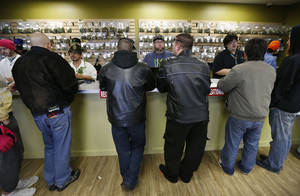 "Photo - Employees help customers at the crowded sales counter inside Medicine Man marijuana retail store, which opened as a legal recreational retail outlet in Denver on Wednesday Jan. 1, 2014. Colorado began retail marijuana sales on Jan. 1, a day some are calling ""Green Wednesday."" (AP Photo/Brennan Linsley)"