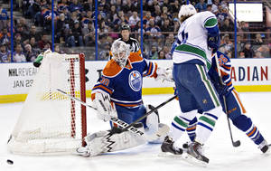 Photo - Vancouver Canucks' Kellan Lain (54) battles in front with Edmonton Oilers' Mark Arcobello (26) as goalie Ben Scrivens (30) makes the save during first period NHL hockey action in Edmonton, Canada, on Tuesday, Jan. 21, 2014. (AP Photo/The Canadian Press, Jason Franson)