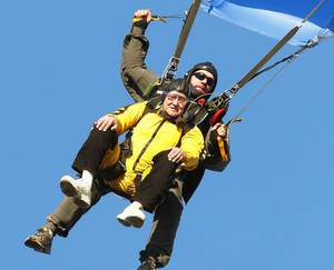 Photo - Warren Crawford enjoys the ride and the view as he and his sky diving partner, Andy Beck, come in for a landing Saturday afternoon at Oklahoma Skydiving Center in Cushing. Photo by Jim Beckel, The Oklahoman