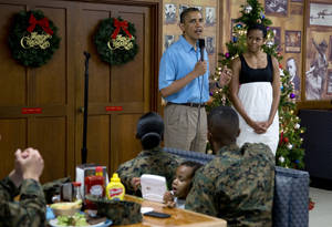 Photo - President Barack Obama speaks as first lady Michelle Obama listens during a visit with members of the military and their families in Anderson Hall at Marine Corp Base Hawaii, Tuesday, Dec. 25, 2012, in Kaneohe Bay, Hawaii. The first family is in Hawaii for a holiday vacation. (AP Photo/Carolyn Kaster)