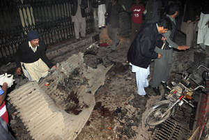 photo - Pakistani plainclothes police officers and local residents examine at the site of a suicide bombing in Peshawar, Pakistan, Saturday, Dec. 22, 2012. A suicide bomber in Pakistan killed several people including a provincial government official at a political rally held Saturday by a party that has opposed the Taliban, officials said. (AP Photo/Sohail Iqbal)