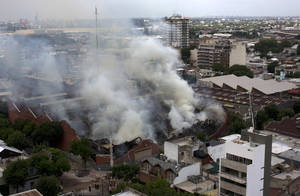 Photo - Smoke rises from the Iron Mountain warehouse in Buenos Aires, Argentina, Wednesday, Feb. 5, 2014. Nine first-responders were killed in the fire that destroyed an archive of bank documents, according to authorities. (AP Photo/Rodrigo Abd)