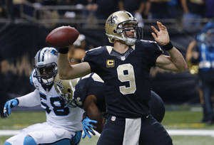Photo - New Orleans Saints quarterback Drew Brees (9) passes under pressure from Carolina Panthers outside linebacker Thomas Davis (58) in the first half of an NFL football game in New Orleans, Sunday, Dec. 8, 2013. (AP Photo/Bill Haber)