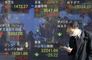 photo - A man checks his mobile phone in front of an electronic stock board of a securities firm in Tokyo Thursday, Dec. 6, 2012 as Japan&#039;s Nikkei 225 index, top center, rose 78.60 points to 9,547.44.  Asian stock markets remained in a holding pattern Thursday as investors assessed President Barack Obama&#039;s comments that reaching a budget deal to prevent the U.S. from a possible recession was &quot;not that tough&quot; and could even be done quickly. (AP Photo/Koji Sasahara)
