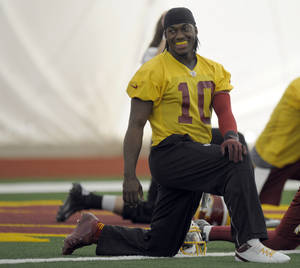 Photo - Washington Redskins quarterback Robert Griffin III stretches during a team workout at Redskins Park in Ashburn, Va., Wednesday, Jan. 2, 2013. The Redskins are working out before Sunday's wild card game against the Seattle Seahawks. (AP Photo/Susan Walsh)