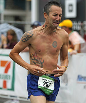 photo - Rick Uribe reacts as he finishes the Oklahoma City Memorial Marathon in Oklahoma City, Sunday, April 29, 2012. Photo by Bryan Terry, The Oklahoman
