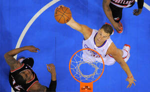 Photo - Los Angeles Clippers forward Blake Griffin goes up for a dunk as Portland Trail Blazers forward LaMarcus Aldridge watches during the first half of an NBA basketball game, Wednesday, Feb. 12, 2014, in Los Angeles. (AP Photo/Mark J. Terrill)