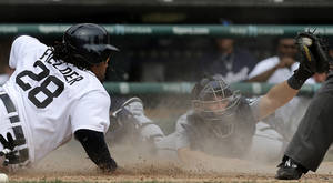 Photo - Detroit Tigers' Prince Fielder (28) slides home safely past the tag of Seattle Mariners catcher Mike Zunino, right, in the seventh inning of a baseball game in Detroit, Thursday, Sept. 19, 2013.  (AP Photo/Paul Sancya)
