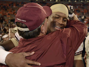 Photo - Florida State quarterback Jameis Winston, right, embraces Florida State head coach Jimbo Fisher after the second half of an NCAA college football game against Clemson, Sunday, Oct. 20, 2013, in Clemson, S.C. Florida State won 51-14. (AP Photo/Richard Shiro)