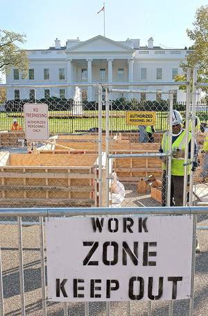 Photo - A construction worker locks the gate behind him as work continues earlier this month in front of the White House in Washington in preparation for President Barack Obama's second inauguration in January.  AP Photo