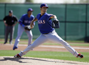 Photo - Texas Rangers pitcher Yu Darvish (11) of Japan delivers to the plate in an intrasquad game during spring training baseball practice, Monday, Feb. 24, 2014, in Surprise, Ariz. (AP Photo/Tony Gutierrez)