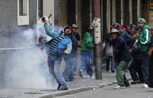 Photo - A demonstrator returns a tear gas canister fired by police during a protest by striking miners in La Paz, Bolivia, Thursday, May 16, 2013. Workers from the workers union Central Obrera Boliviana (COB) began an indefinite strike on May 6 to demand the government of President Evo Morales improve the pension law. (AP Photo/Juan Karita)