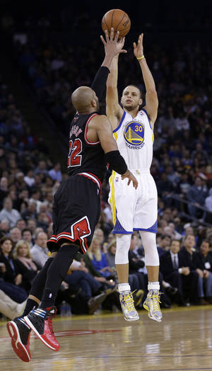 Photo - Golden State Warriors' Stephen Curry (30) makes a three-point basket over Chicago Bulls' Taj Gibson during the second half of an NBA basketball game on Thursday, Feb. 6, 2014, in Oakland, Calif. Golden State won 102-87. (AP Photo/Marcio Jose Sanchez)