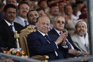 Photo -   Yemeni President Abed Rabbu Mansour Hadi claps as he watches a parade during a ceremony to commemorate the 22nd anniversary of Yemen's reunification, in Sanaa, Yemen, Tuesday, May 22, 2012. Yemeni leaders led a somber ceremony Tuesday to mark the country's national day, scaling back the celebrations a day after a suicide bombing killed tens of soldiers during a rehearsal for a military parade. (AP Photo/Hani Mohammed)