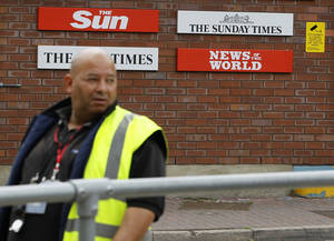 Photo - FILE - This is a Thursday, July 14, 2011 file photo of  a security guard keeps watch at News International in Wapping, London. Former News of the World editor Andy Coulson was convicted of phone hacking Tuesday, but fellow editor Rebekah Brooks was acquitted after a months long trial centering on illegal activity at the heart of Rupert Murdoch's newspaper empire. The News of the World closed, because of the phone hacking scandal.  (AP Photo/Kirsty Wigglesworth, File)