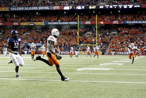 photo - Oklahoma State's Justin Blackmon (81) tip-toes the goal line before scoring a touchdown in front of Arizona's Adam Hall (12) during the Valero Alamo Bowl college football game between the Oklahoma State University Cowboys (OSU) and the University of Arizona Wildcats at the Alamodome in San Antonio, Texas, Wednesday, December 29, 2010. Photo by Sarah Phipps, The Oklahoman ORG XMIT: KOD