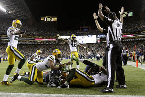 Photo -   Officials signal after Seattle Seahawks wide receiver Golden Tate pulled in a last-second pass from quarterback Russell Wilson to defeat the Green Bay Packers 14-12 in an NFL football game, Monday, Sept. 24, 2012, in Seattle. The touchdown call stood after review. (AP Photo/The Seattle Times, John Lok) MAGS OUT; NO SALES; SEATTLEPI.COM OUT; MANDATORY CREDIT; USA TODAY OUT; TV OUT