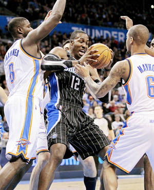photo - Oklahoma City Thunder's Nazr Mohammed (8) and Oklahoma City Thunder's Eric Maynor (6) guard Orlando Magic's Dwight Howard (12) in the first half as the Oklahoma City Thunder play the Orlando Magic in NBA basketball at the Chesapeake Energy Arena on Sunday, Dec. 25, 2011, in Oklahoma City, Okla. Photo by Steve Sisney, The Oklahoman
