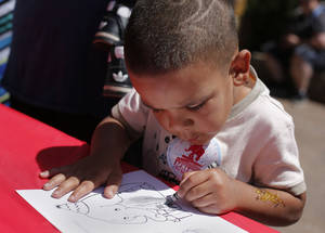 Photo - Kevin Parks, 5, of Oklahoma City, colors a picture of an elephant during Malee's party.