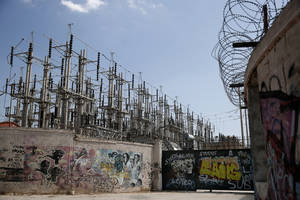 Photo - Graffiti is painted on walls and the entrance of an electric station of Public Power Corporation (PPC) in Athens, on Wednesday, July 2, 2014. PPC workers are threatening with rolling strikes to protest government plans to sell a stake in the company to private investors. The conservative-led government is warning that a protracted strike could lead to blackouts at the height of Greece's key tourist season, and has said it could try to force PPC workers back to work through a mobilization order. (AP Photo/Petros Giannakouris)