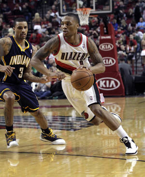 Photo - Portland Trail Blazers guard Damian Lillard, right, drives on Indiana Pacers guard George Hill during the first quarter of an NBA basketball game in Portland, Ore., Wednesday, Jan. 23, 2013. (AP Photo/Don Ryan)