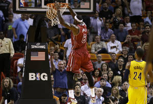 Photo - Miami Heat's LeBron James dunks as Indiana Pacers' Paul George (24) watches during the first half of an NBA basketball game, Wednesday, Dec. 18, 2013, in Miami. (AP Photo/Lynne Sladky)