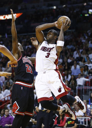 photo - Chicago Bulls Jimmy Butler (21) forces Miami Heat's Dwyane Wade (3) to pass the ball during the first half of a NBA basketball game in Miami, Friday, Jan. 4, 2013. (AP Photo/J Pat Carter)