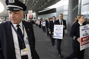 "photo -   FILE- In this Thursday, Sept. 20, 2012, file photo, Captain Mike McClellan, ORD Domicile Chairman of the Allied Pilots Association left, joins over 200 American Airline pilots marching on a picket line at O'Hare International Airport, in Chicago. American Airlines said Thursday, Sept. 27, 2012, if pilots don't end actions that are disrupting its flights, it will take their union to court. A top American Airlines executive told union leaders that some pilots were conducting ""an unlawful, concerted effort to damage the company"" by filing more maintenance complaints and other tactics, leading to a surge in late and canceled flights.(AP Photo/M. Spencer Green, File)"