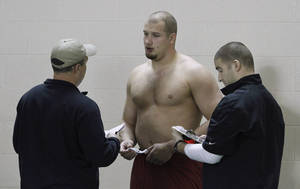 photo - Offensive lineman Lane Johnson talks with NFL scouts during Oklahoma's NFL football pro day in Norman, Okla., Wednesday, March 13, 2013. (AP Photo/Alonzo Adams)