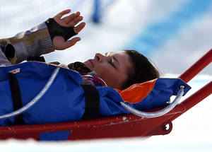 Photo - Jacqueline Hernandez of the United States is carried off the course in a stretcher after crashing in a seeding run during women's snowboard cross competition at the Rosa Khutor Extreme Park, at the 2014 Winter Olympics, Sunday, Feb. 16, 2014, in Krasnaya Polyana, Russia. (AP Photo/Sergei Grits)