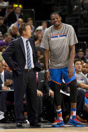 Photo - Oklahoma City Thunder's Kevin Durant, right, stands with Head Coach Scott Brooks during the team's NBA preseason basketball game against Philadelphia 76ers at the Phones 4u Arena in Manchester, England, Tuesday, Oct. 8, 2013. (AP Photo/Jon Super) ORG XMIT: MJS109