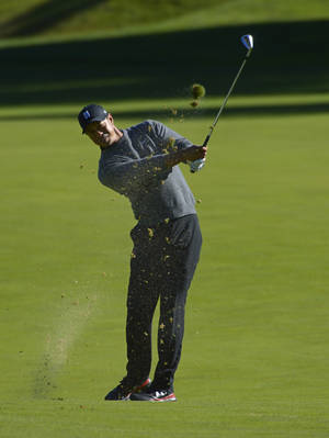 Photo - Tiger Woods makes his approach shot on the 11th hole during the pro-am portion of the Northwestern Mutual World Challenge, Wednesday, Dec. 4, 2013, in Thousand Oaks, Calif. (AP Photo/Mark J. Terrill)