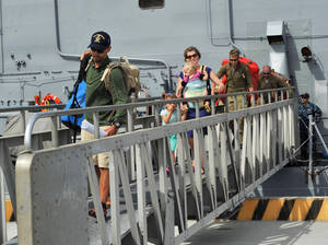 Photo - This photo provided by the U.S. Navy shows the Kaufman family disembarking from the USS Vandegrift on Wednesday, April 9, 2014, at Naval Air Station North Island in San Diego, following their rescue at sea on April 6.  Six days after the family of four found themselves helpless and adrift in a sailboat far into the Pacific with a vomiting and feverish 1-year-old aboard, a Navy warship delivered them safely to shore, where they had begun their attempted around-the world voyage before the child was born. (AP Photo/U.S. Navy)