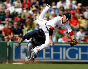 photo - Boston Red Sox third baseman Will Middlebrooks, right, leaps as he misses a throw from catcher Jarrod Saltalamacchia allowing Tampa Bay Rays' Desmond Jennings, left, to score from third base during the third inning of an exhibition spring training baseball game, Saturday, Feb. 23, 2013, in Fort Myers, Fla. (AP Photo/David Goldman)