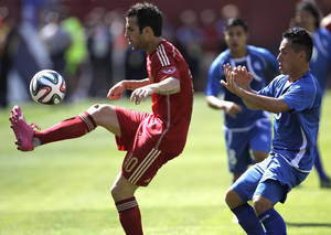 Photo - Spain's Cesc Fabregas, left, kicks the ball as El Salvador's Richard Menjivar, right, defends during the first half of an exhibition soccer game, Saturday, June 7, 2014, in Landover, Md. Spain won 2-0. (AP Photo/Luis M. Alvarez)