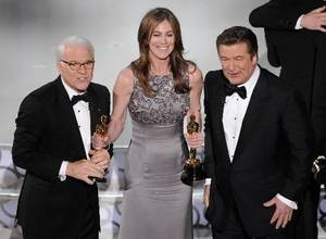 "Photo - Kathryn Bigelow, center, holds her Oscars for best motion picture of the year and best achievement in directing for ""The  Hurt  Locker"" with hosts Alec Baldwin, right, and Steve Martin at the conclusion of the 82nd Academy Awards Sunday, March 7, 2010, in the Hollywood section of Los Angeles. (AP Photo/Mark J. Terrill)"