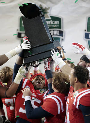 Photo - Mississippi defensive back Ontario Berry (35) lifts up the winners' trophy after beating Georgia Tech in the Music City Bowl on Monday, Dec. 30, 2013, in Nashville, Tenn. Mississippi won 25-17. (AP Photo/Mark Humphrey)