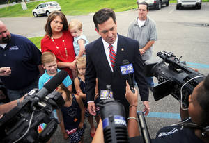 Photo - State Sen. Chris McDaniel speaks with the media before voting at the George Harrison Building, Tuesday, June 24, 2014, in Ellisville, Miss. Voters go to the polls Tuesday to vote in the Republican primary runoff election between incumbent Sen. Thad Cochran and challenger McDaniel. The winner will face Democrat Travis Childers in the November general election. McDaniel's wife Jill and family listen at rear left. (AP Photo/The Hattiesburg American, Bryant Hawkins)  NO SALES