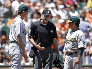 Photo - Home plate umpire Angel Hernandez, center, talks with Oakland Athletics manager Bob Melvin, left, and third base coach Mike Gallego, right, in the fourth inning of their interleague baseball game against the San Francisco Giants Thursday, July 10, 2014, in San Francisco. Hernandez replaced umpire Adrian Johnson who left the game earlier in the inning. (AP Photo/Eric Risberg)