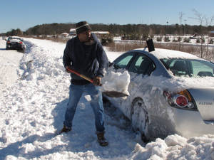 Photo - Dennis Lawrence spent several hours digging out his car from the side of Sunrise Highway in Patchogue, N.Y., on Sunday, Feb. 10, 2013. Lawrence was one of hundreds of drivers who became stranded when a blizzard left as much as 30 inches of snow on Long Island.(AP Photo/Frank Eltman)