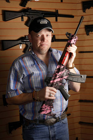 photo - Mike Blackwell, owner of Big Boy's Guns and Ammo, shows a pink Smith & Wesson rifle. <strong>Steve Gooch - The Oklahoman</strong>