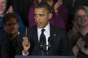 photo -   President Barack Obama holds up a pen as he speaks about the economy and the deficit, Friday, Nov. 9, 2012, in the East Room of the White House in Washington. (AP Photo/Carolyn Kaster)