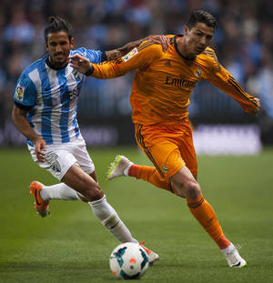Photo - Real Madrid's Cristiano Ronaldo, right, duels for the ball against CF Malaga's Marcos Alberto Angeleri, left, during a Spanish La Liga soccer match at La Rosaleda stadium in Malaga, Spain, Saturday March 15, 2014. (AP Photo/Daniel Tejedor)